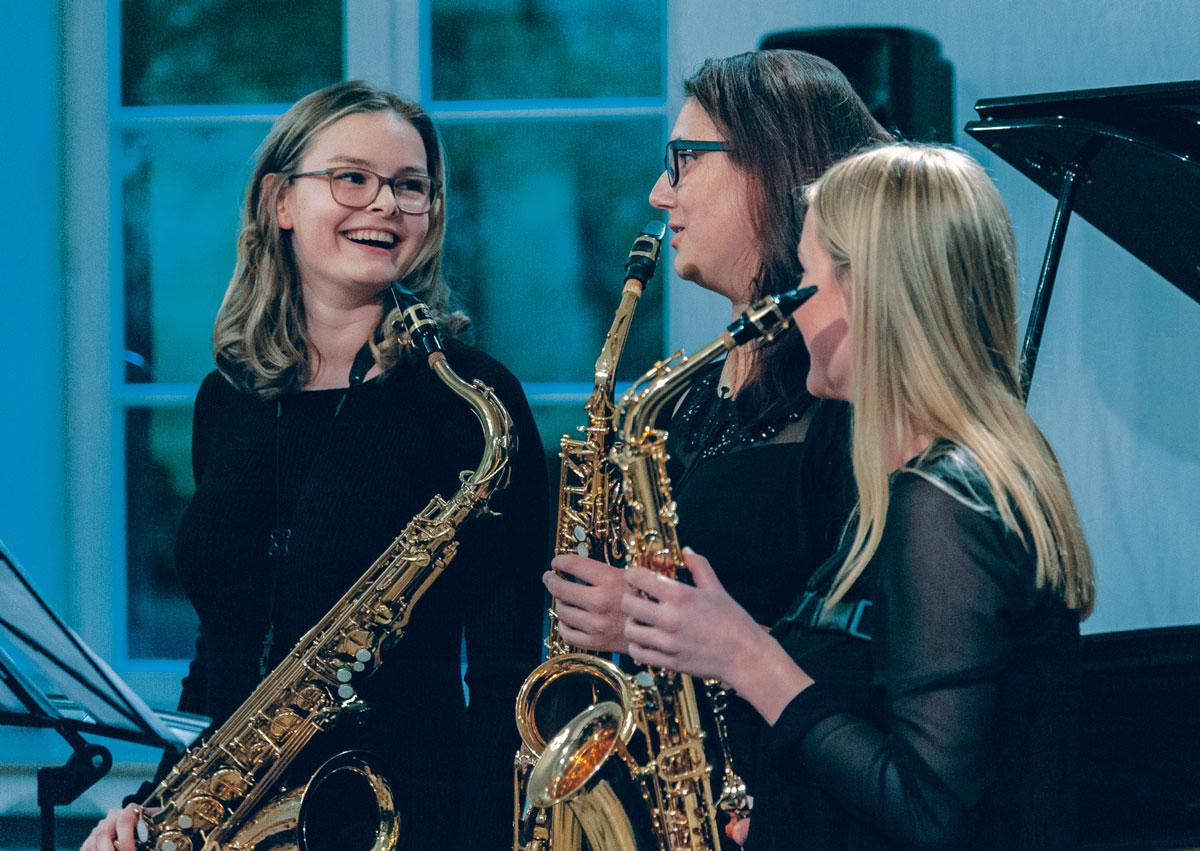 Drei lachende junge Frauen mit Saxophon beim Konzertabend der Musikschule rhythm matters
